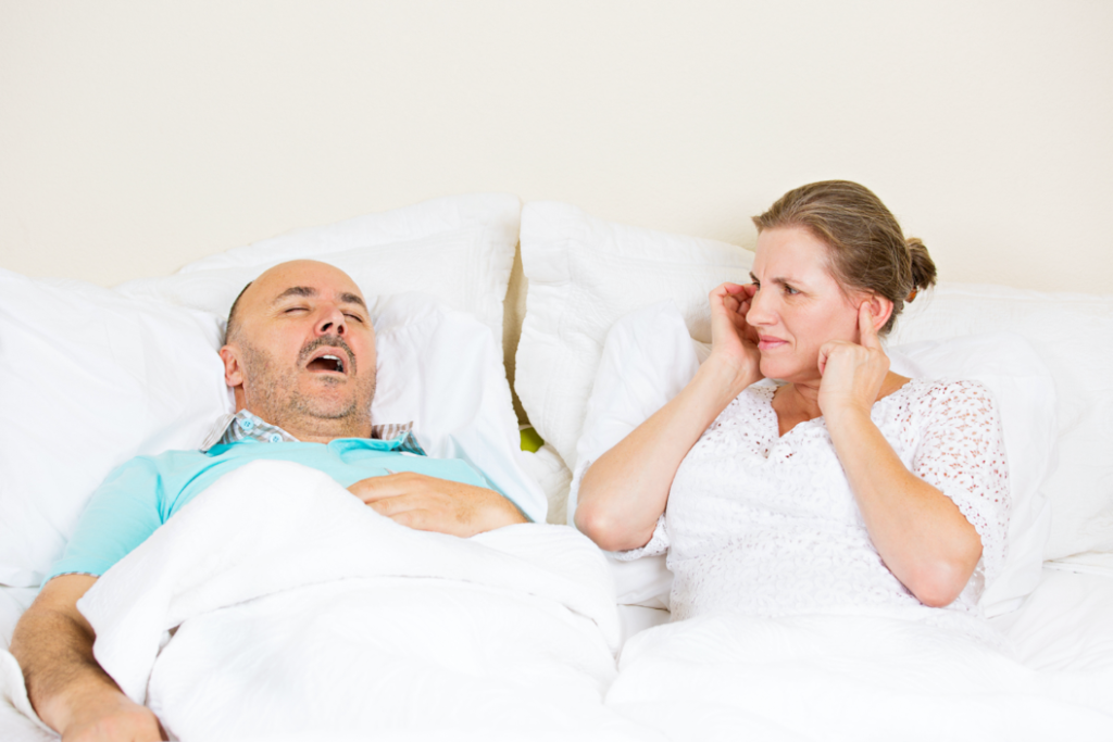 man in bed snoring, annoyed woman plugging ears