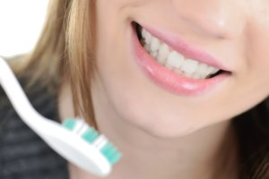 woman with strong teeth enamel smiling with toothbrush