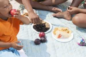 Family having a picnic at the beach with summer treats that can damage teeth