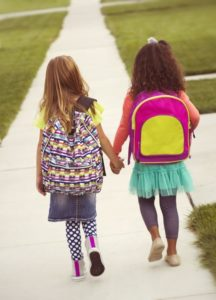 back-to-school photo of girls walking to school with backpacks